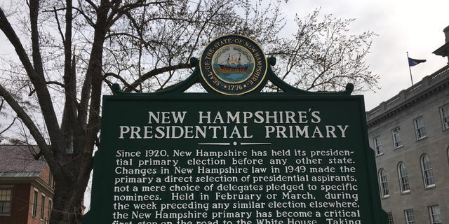 A sign next to the Statehouse in Concord, NH highlights that New Hampshire's held the first-in-the-nation presidential primary for 100 years