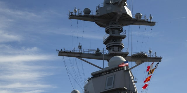 USS Gerald R. Ford (CVN 78) raising the American flag on its mast, this past February.