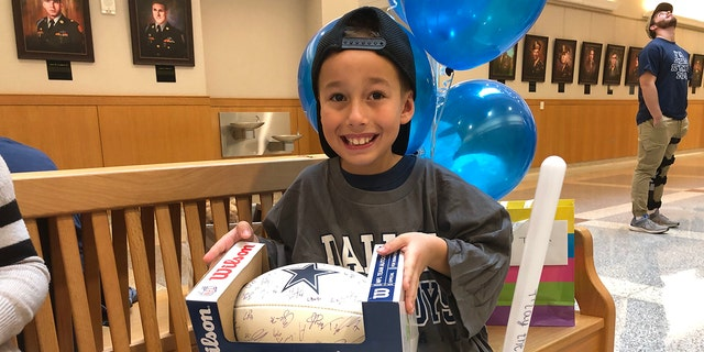 Nike got a huge surprise when he was gifted with a football signed by his favorite NFL player, Cowboys quarterback Dak Prescott and the entire 2019 Cowboys team. (Photo: Courtesy of Buckner International)