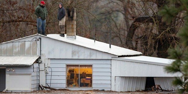 Feb. 6, 2020: Nate Fuller and Archie Morrow await rescue on the roof of a home in Thorn Hollow outside of Adams, Ore.