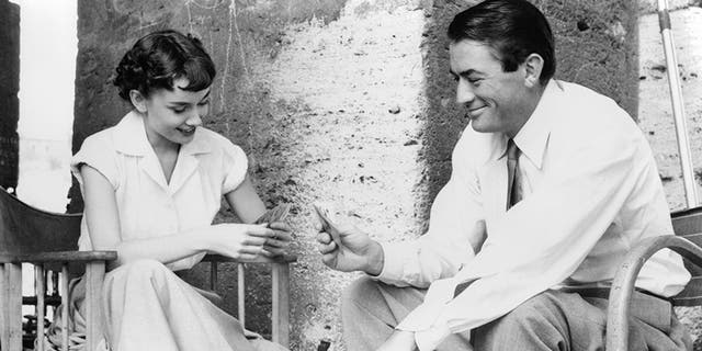"""Audrey Hepburn plays cards with Gregory Peck in a scene from the film """"Roman Holiday,"""" 1953."""