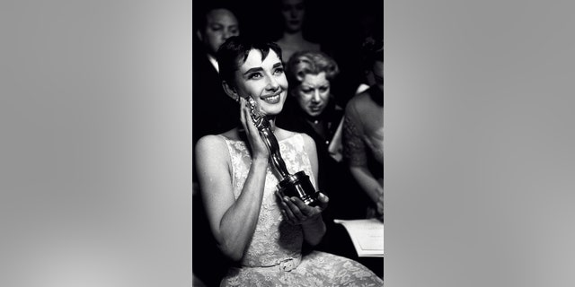 Actress Audrey Hepburn affectionately holding Oscar award she won for her performance in the movie 'Roman Holiday' at the Academy Awards ceremony in New York City.