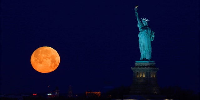 The almost full Snow Moon sets beside the Statue of Liberty before sunrise on February 8, 2020 in New York City.