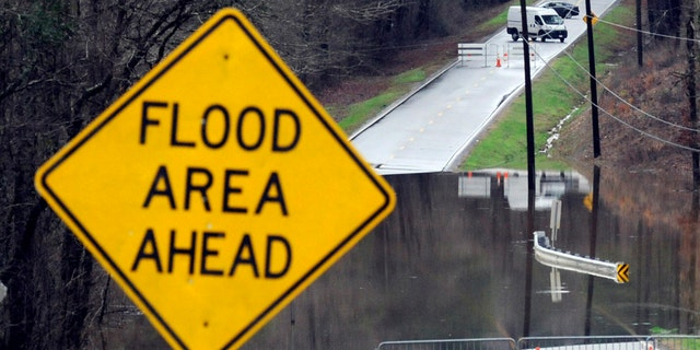 Vehicles turn around on a road blocked by floodwaters in Helena, Ala., on Tuesday, Feb. 11, 2020.