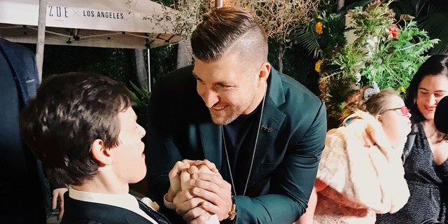Micah Fowler meeting Tim Tebow on the red carpet at Zoe Church鈥檚 Night to Shine in 2019.