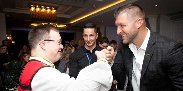 "Tim Tebow fist bumps a guest at the ""Night to Shine"" in Albania."