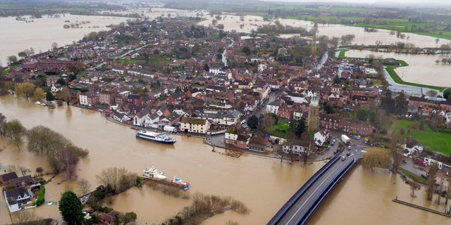 Floodwater surrounds the town of Upton-upon-Severn, England, with the normal course of the river Severn running horizontally under the road bridge, in the aftermath of Storm Dennis, in this photo taken with a drone Thursday, Feb. 20, 2020.
