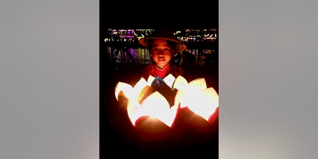 A young girl in Hoi An sells lanterns on what was once a bustling lantern-lit riverwalk.