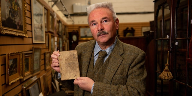 Militaria expert Adrian Stevenson of Hansons Auctioneers holds the diary written by British World War I soldier Arthur Edward Diggens.