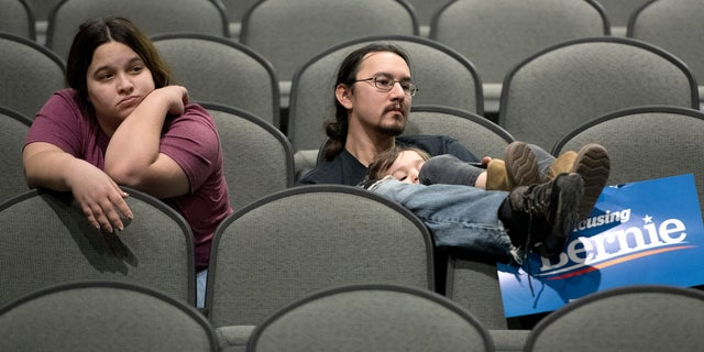 Jeff Lopez holds his son, Tristan, 4, as they and Jeff's wife, Jessika, sit in an area for Bernie Sanders supporters during the Woodbury County Third Precinct Democratic caucus, Monday, Feb. 3, 2020, at West High School in Sioux City, Iowa. Iowans across the state attended Democratic and Republican caucuses Monday. (Tim Hynds/Sioux City Journal via AP)