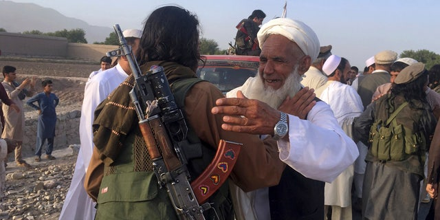 In this June 16, 2018 file photo, Taliban fighters gather with residents to celebrate a three-day cease fire marking the Islamic holiday of Eid al-Fitr, in Nangarhar province, east of Kabul, Afghanistan.  (AP Photo/Rahmat Gul, File)