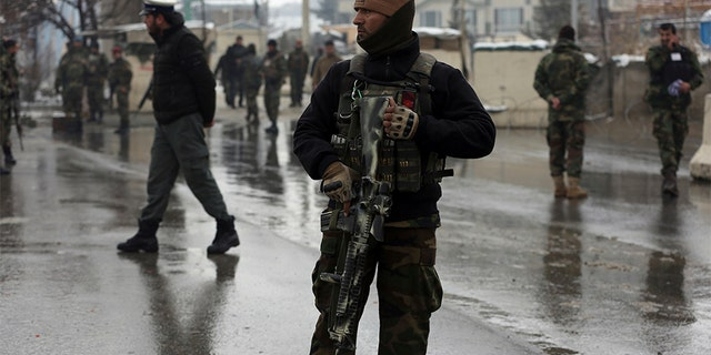 Afghan soldiers stand guard at the site of a suicide attack near the military academy in Kabul, Afghanistan, on Tuesday. A suicide bomber targeting a military academy in the Afghan capital killed at least six people, including two civilians and four military personnel, the Interior Ministry said. (AP)