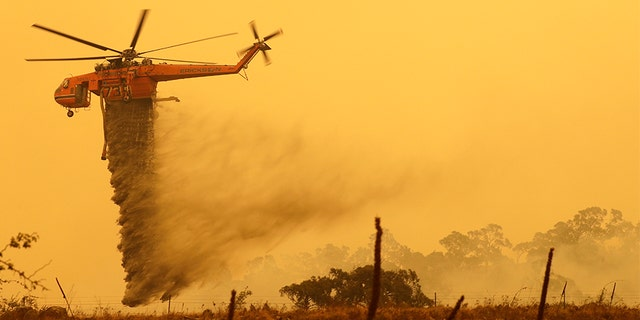 A helicopter drops water on a fire near Bumbalong, south of the Australian capital of Canberra, on Feb. 1, 2020.