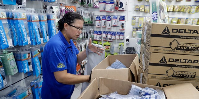 A medical supply store worker organizes masks that customers are buying as a precaution against the spread of the coronavirus in Sao Paulo, Brazil.