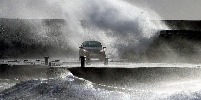 Waves lash the coast on the Ayrshire coast at Ardrossan, Scotland, Sunday, Feb. 9, 2020.