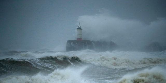 Waves crash over the harbour and a lighthouse, as Storm Ciara hits Newhaven, on the south coast of England, Sunday, Feb. 9, 2020.