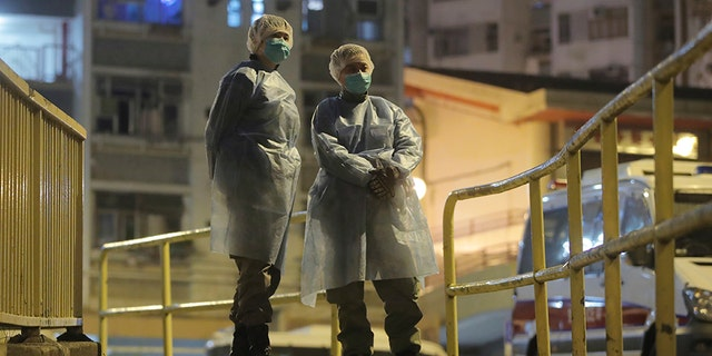 People wearing protective suits stand near the Cheung Hong Estate, a public housing estate, during the evacuation of residents in Hong Kong on Tuesday. (AP)