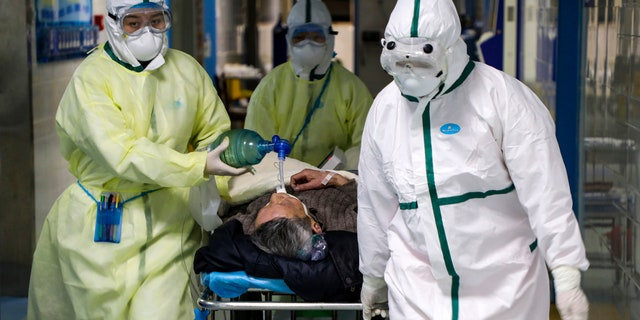 In this Thursday, Feb. 6, 2020, photo, medical workers transfer a patient in the isolation ward for 2019-nCoV patients at a hospital in Wuhan in central China's Hubei province.