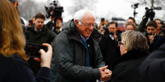Democratic presidential candidate Sen. Bernie Sanders, I-Vt., meets with people outside a polling place where voters will cast their ballots in a primary election, in Manchester, N.H., Tuesday, Feb. 11, 2020. (AP Photo/Matt Rourke)