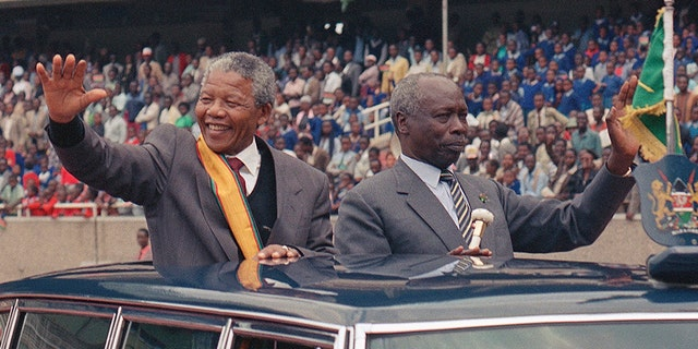 South African leader Nelson Mandela, left, and Kenya President Daniel arap Moi wave to the crowd at a public rally for the African National Congress in Nairobi, Kenya, in 1993. (AP)