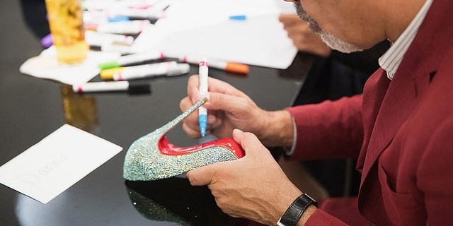 """Louboutin, seen here signing his signature shoes during an appearance at a Nordstrom in Seattle, said he was always drawn to the""""mystery and the fetishistic side"""" of the heels."""