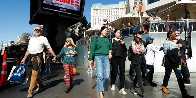 People walk near the Paris Las Vegas hotel casino, site of a Democratic presidential debate, Wednesday, Feb. 19, 2020, in Las Vegas. (AP Photo/John Locher)