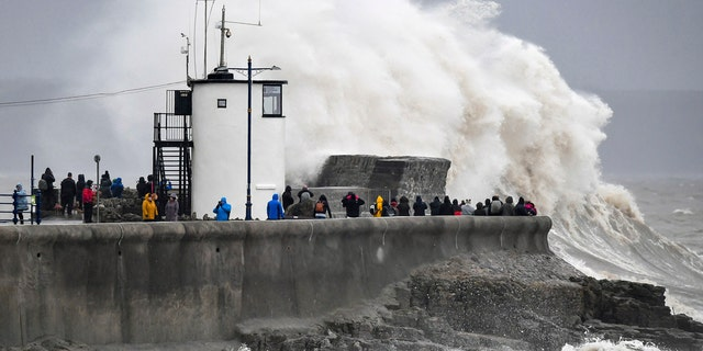 People watch waves and rough seas pound against the harbor wall at Porthcawl in Wales, as Storm Dennis sweeps across the country, Saturday Feb. 15, 2020.