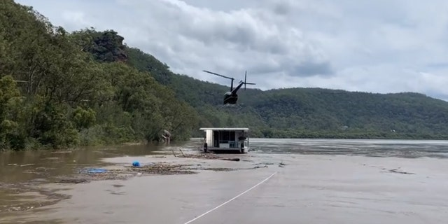 A helicopter touches down on a houseboat in Australia that drifted down a flooded river on Monday.