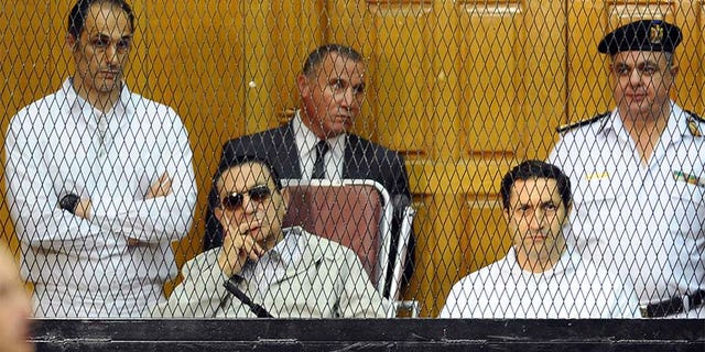 Former Egyptian President Hosni Mubarak, seated center left, and his two sons, Gamal Mubarak, left, and Alaa Mubarak attend a hearing in a courtroom in Cairo, Egypt, in 2013. (AP)