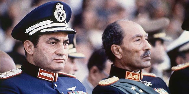 In this 1981 file photo, Egyptian President Anwar Sadat, right, and Vice President Hosni Mubarak sit on the reviewing stand during a military parade just before soldiers opened fire from a truck during the parade at the reviewing stand, killing Sadat and injuring Mubarak.