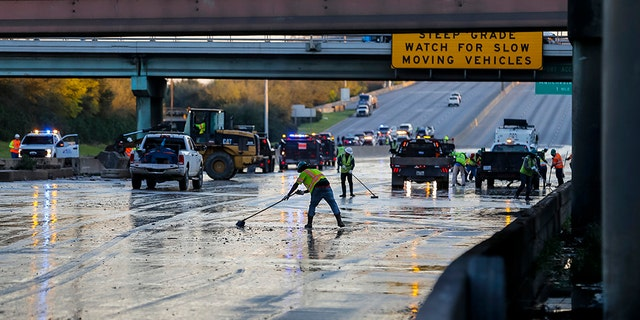 Workers clean water from the southbound lanes of 610 at Clinton Drive, Thursday, Feb. 27, 2020, in Houston. (Associated Press)