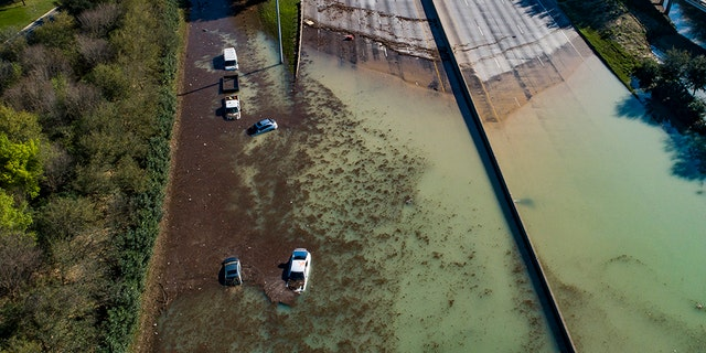 In this aerial photo, water is slowly draining from the freeway after a water main break east of the location flooded all lanes, closing the freeway in both directions, at the intersection of 610 and Clinton Drive, Thursday, Feb. 27, 2020. (Associated Press)