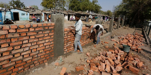 Indian workers construct a wall in front of a slum ahead of U.S. President Donald Trump's visit, in Ahmadabad, India, Monday, Feb. 17, 2020. Trump is scheduled to visit the city during his Feb. 24-25 India trip. (AP Photo/Ajit Solanki)