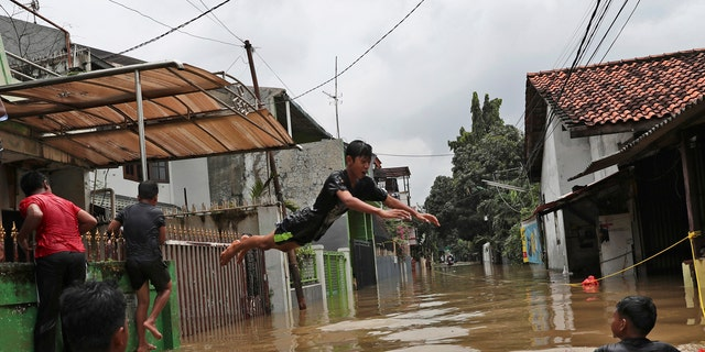 Indonesian youths play in flood water in a neighborhood in Jakarta, Indonesia, Tuesday, Feb. 25, 2020.
