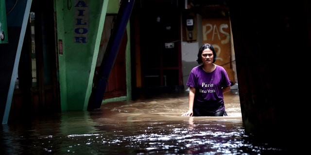 A woman wades through water in a flooded neighborhood in Jakarta, Indonesia, Tuesday, Feb. 25, 2020.