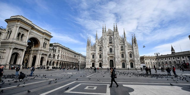 A small number of people walk through the usually bustling Piazza Duomo in Milan on Wednesday. (Claudio Furlan/LaPresse via AP)