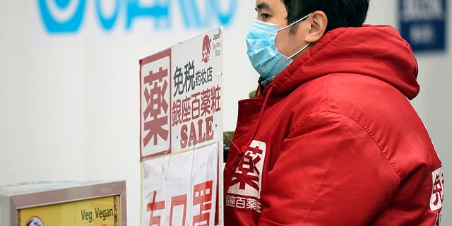 "A man holds a shop advertisement saying ""We have masks"" in Ginza shopping district Wednesday in Tokyo."