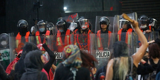 Riot police form a cordon during a demonstration by women against gender violence in Mexico City on Friday. (AP)