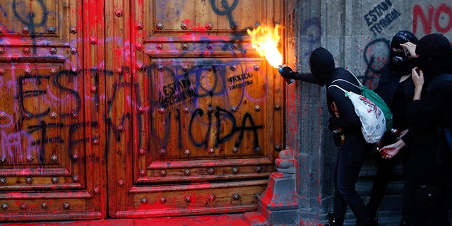 A masked protester sprays fire at the entrance to the National Palace, the presidential office and residence, after demonstrators covered it in fake blood and the Spanish message: