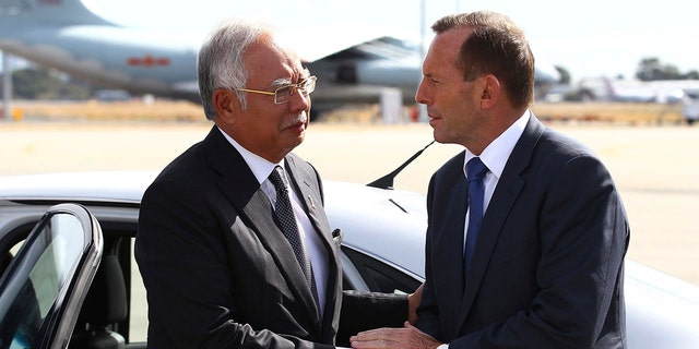 In this April 3, 2014, file photo, Australian then Prime Minister Tony Abbott, right, shakes hands with Malaysian then Prime Minister Najib Razak as Razak prepares to depart Australia after his visit during the search of the missing Malaysia Airlines flight MH370 at Perth International Airport, Australia.