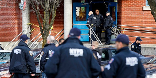 New York City police officers work the scene of a police-involved shooting outside the 41st precinct Sunday in the Bronx. (AP Photo/John Minchillo)