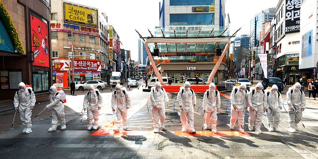 South Korean army soldiers wearing protective suits spray disinfectant to prevent the spread of the COVID-19 virus on a street in Daegu.