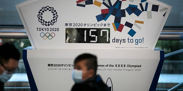 """Two people wearing masks sit in front of a countdown clock for the Tokyo 2020 Olympics on Tuesday. Tokyo Olympic organizers said last week there is no """"Plan B"""" for the 2020 Games, which open in just over five months and have been jolted by the outbreak of the coronavirus in neighboring China."""