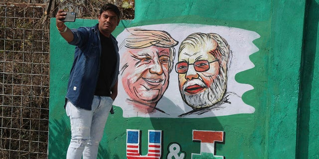 A man takes a selfie with portraits of U.S. President Donald Trump and Indian Prime Minister Narendra Modi painted on a wall ahead of Trump's visit, in Ahmadabad, India, Tuesday, Feb. 18, 2020. Trump is scheduled to visit the city during his Feb. 24-25 India trip. [AP Photo/Ajit Solanki)