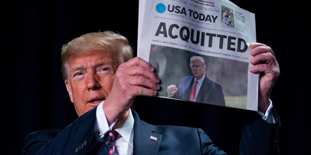 "President Trump holds up a newspaper with the headline that reads ""ACQUITTED"" at the 68th annual National Prayer Breakfast, at the Washington Hilton, Thursday, Feb. 6, 2020, in Washington. (AP Photo/ Evan Vucci)"