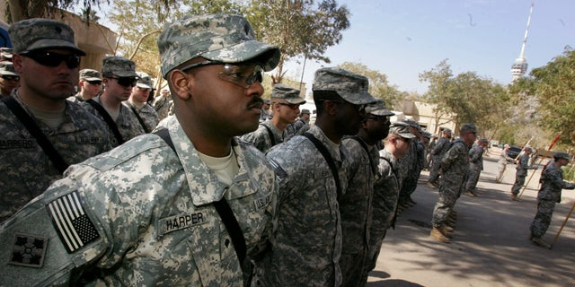 US army soliders from 4/42 Field Artillery Battalion look on during a transfer ceremony in the heavily fortified Green Zone area March 4, 2009 in Baghdad, Iraq.
