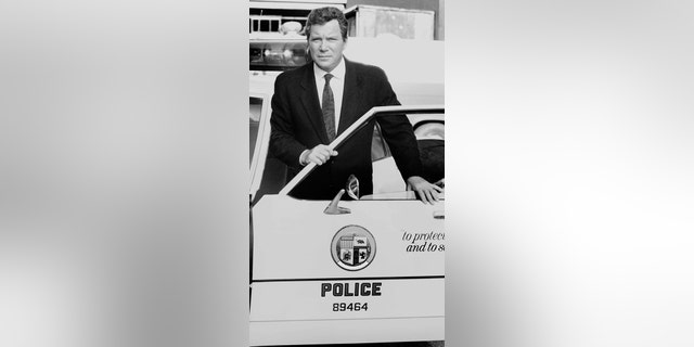 William Shatner stands behind the door of a police car as he hosts the CBS Television true crime program 'Rescue 911.'