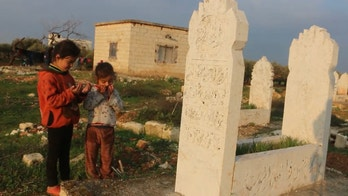 Displaced Syrian family lives in a graveyard as the war enters its 10th year