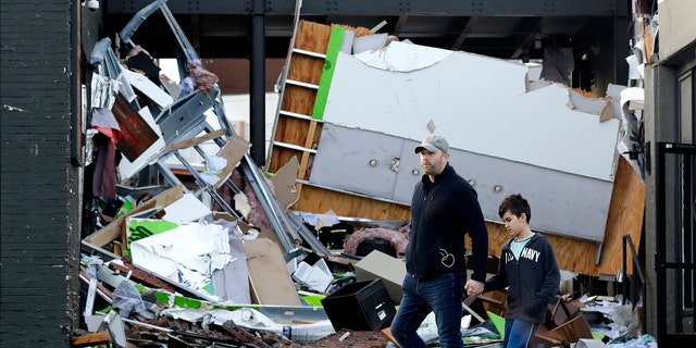 People walk past buildings damaged by storms Tuesday, March 3, 2020, in Nashville, Tenn.