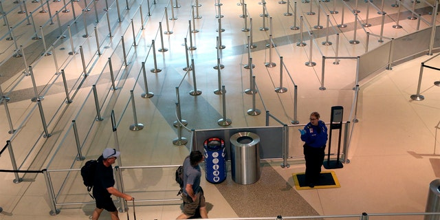 A TSA agent speaks to travelers passing through an empty security queue at Love Field airport in Dallas, Thursday, March 12, 2020, amid concerns of the coronavirus pandemic. (AP Photo/LM Otero)